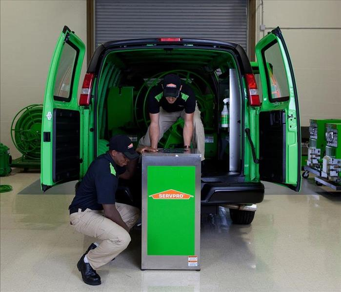 Technicians lowering a humidifier from a van