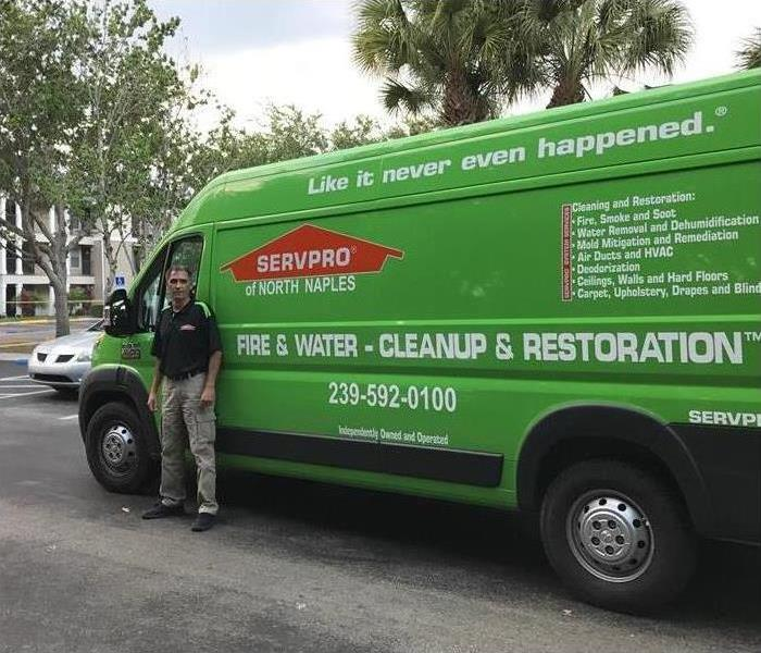 A man standing in front of a  SERVPRO van